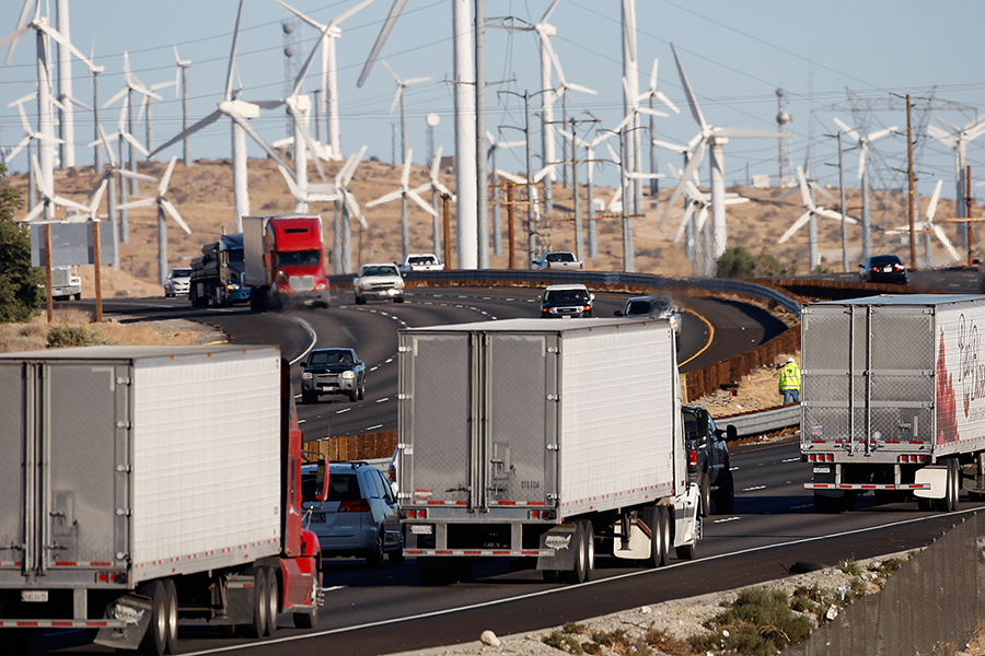 Trucks pass a wind farm in California. Globally, transportation is a major greenhouse gas emitter. Credit: David McNew/Getty Images