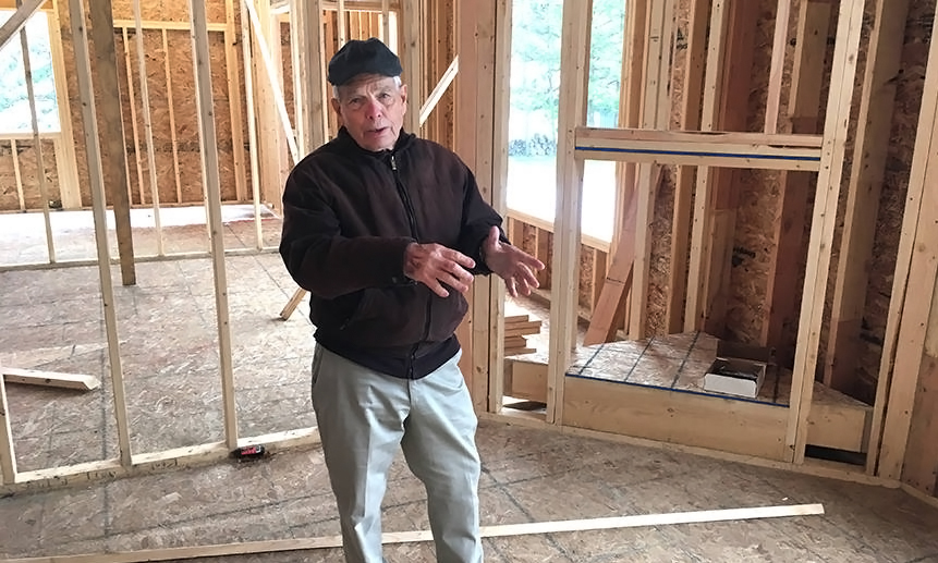 Bill Decker shows some of the building techniques used to create highly energy-efficient homes. Credit: Dan Gearino