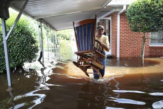 Days of rain from Hurricane Florence flooded homes across a wide area of North Carolina. In Spring Lake, nearly 100 miles from the coast, Bob Richling carried items from a home as the Little River flooded. Credit: Joe Raedle/Getty Images