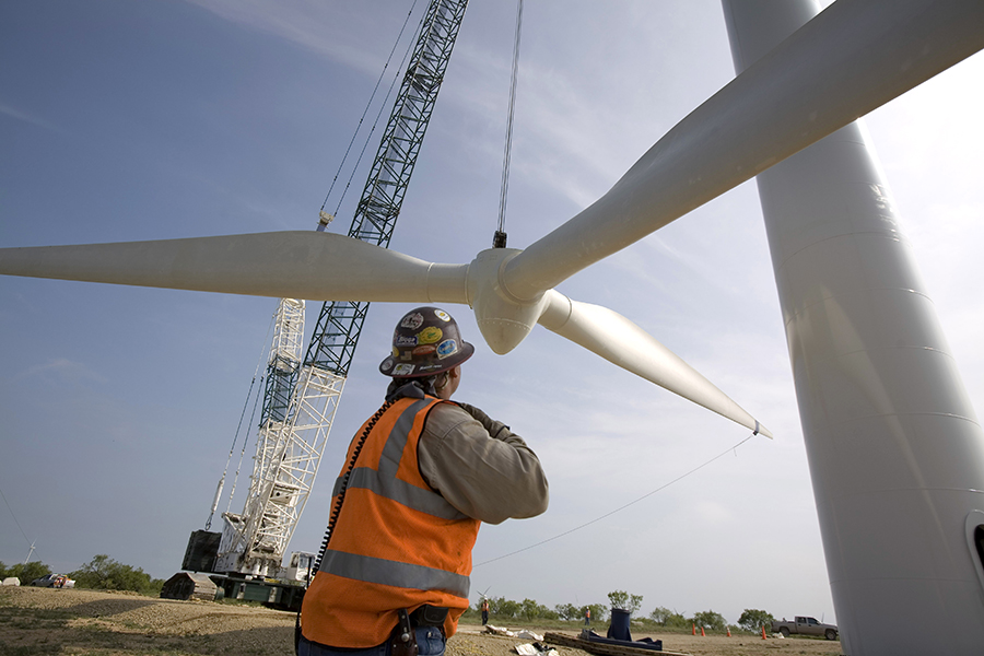 Workers install wind blades on a wind turbine. Credit: Robert Nickelsberg/Getty Images