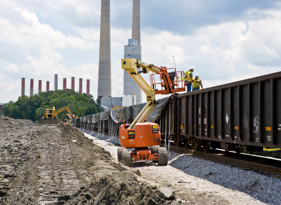Workers prepare to place plastic covers over rail cars with scooped-up coal ash. Credit: TVA