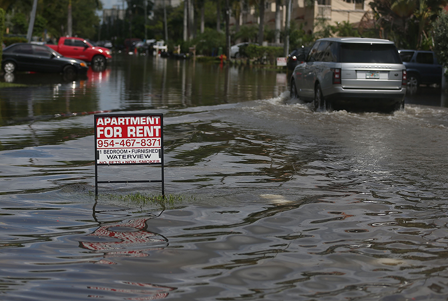 High-tide flooding fills a street in Fort Lauderdale, Florida, making getting to all types of homes harder. Credit: Joe Raedle/Getty Images.