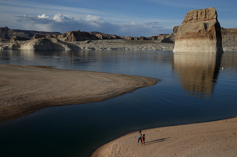 People walk on a beach that used to be the bottom of Lake Powell, a key reservoir on the Colorado River in Utah. Credit: Justin Sullivan/Getty Images