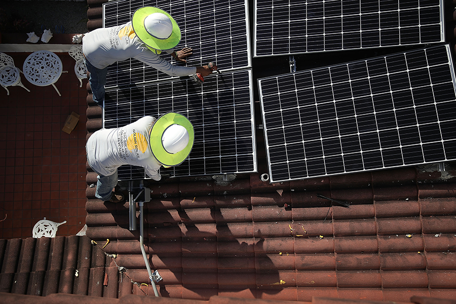 Solar installers work on a home rooftop in Florida. Credit: Joe Raedle/Getty Images