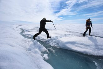 Scientists leap over a meltwater stream on the Greenland Ice Sheet. Credit: Joe Raedle/Getty Images
