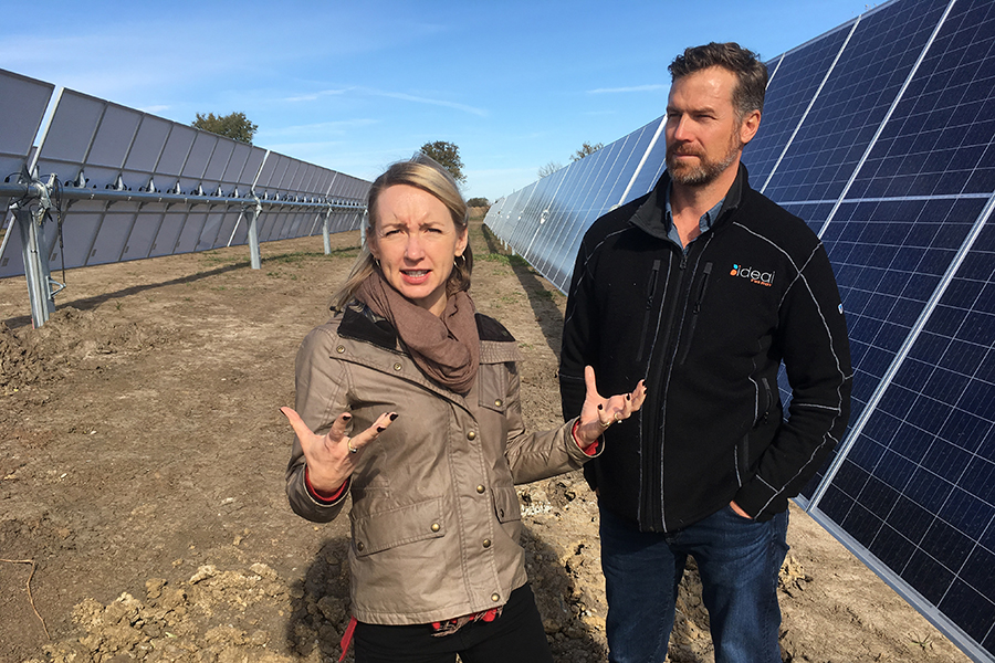 Ideal Solar's owners, Troy and Amy Van Beek, walk among the solar panels at the Maharishi University of Management's solar array. Credit: Dan Gearino/InsideClimate News