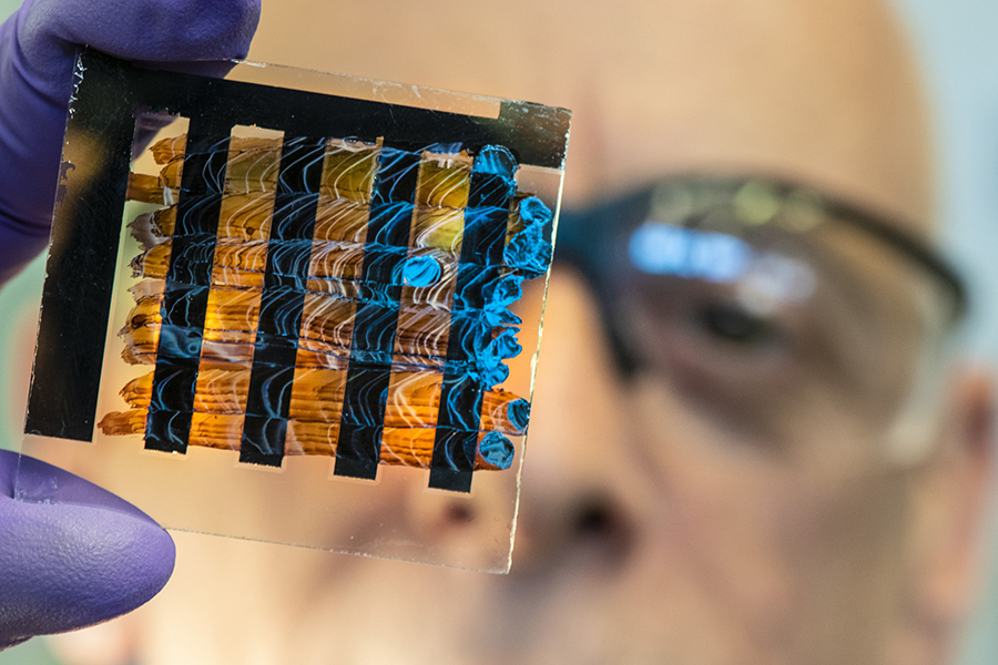 National Renewable Energy Lab researcher David Moore holds a perovskite ink painted solar cell. Credit: Dennis Schroeder/NREL