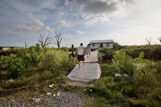 Children run across a bayou bridge to reach their home in Isle de Jean Charles. Credit: Julie Dermansky/Corbis via Getty images