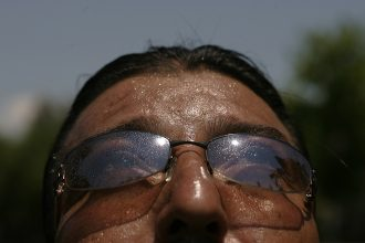 A groundskeeper in Los Angeles sweats through a heat wave. Credit: Anne Cusack/Los Angeles Times via Getty Images
