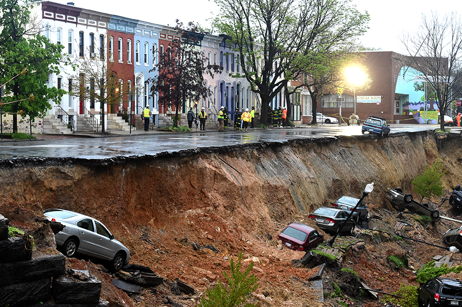A Baltimore street partially collapsed during a week of extreme rainfall in 2014, sending cars and roadway sliding down an embankment. Jonathan Newton/The Washington Post via Getty Images
