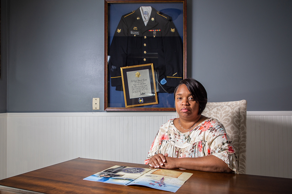 Carolyn McLemore looks at the program from her son's funeral at his home in Memphis. Cayln McLemore died during an Army Reserve training exercise in June 2018. Credit: Brock Stoneham/NBC News