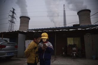 Two boys look at a smartphone in front of their house next to a coal fired power plant on the outskirts of Beijing. Credit: Kevin Frayer/Getty Images