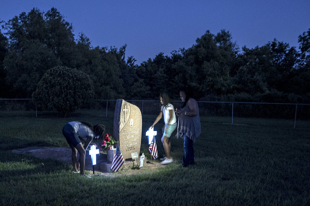 Shirley Cline places glow-in-the-dark crosses at her son's grave at their family plot. Credit: Andrea Morales for NBC News