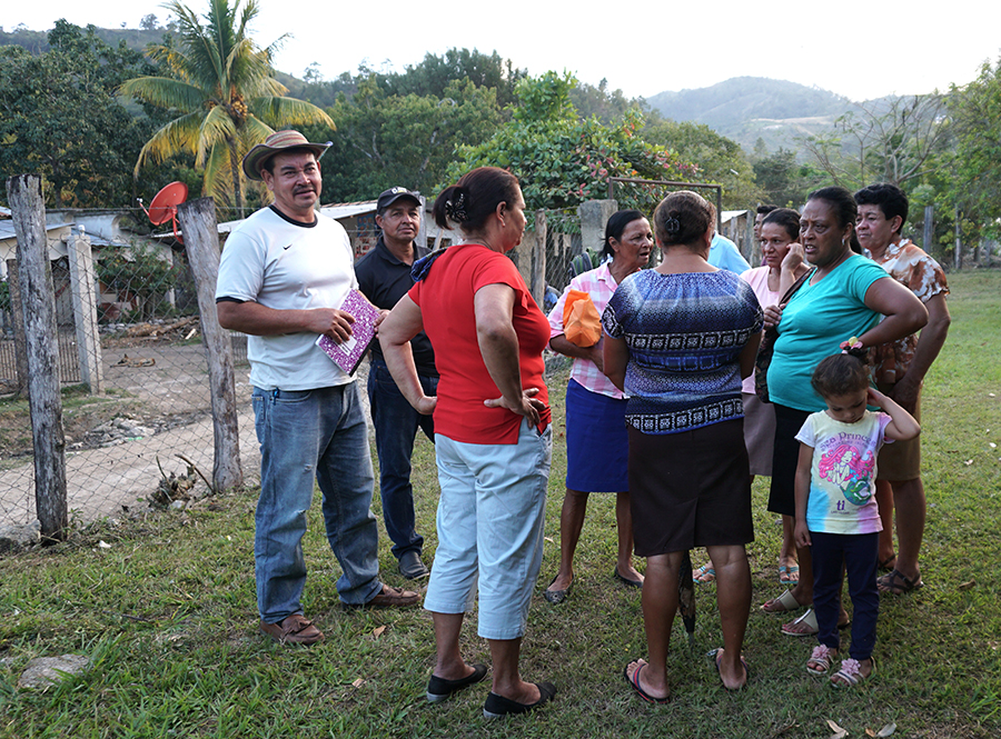 Nelson Meijia (left) talks with his neighbors in El Rosario after the meeting. Credit: Georgina Gustin/InsideClimate News
