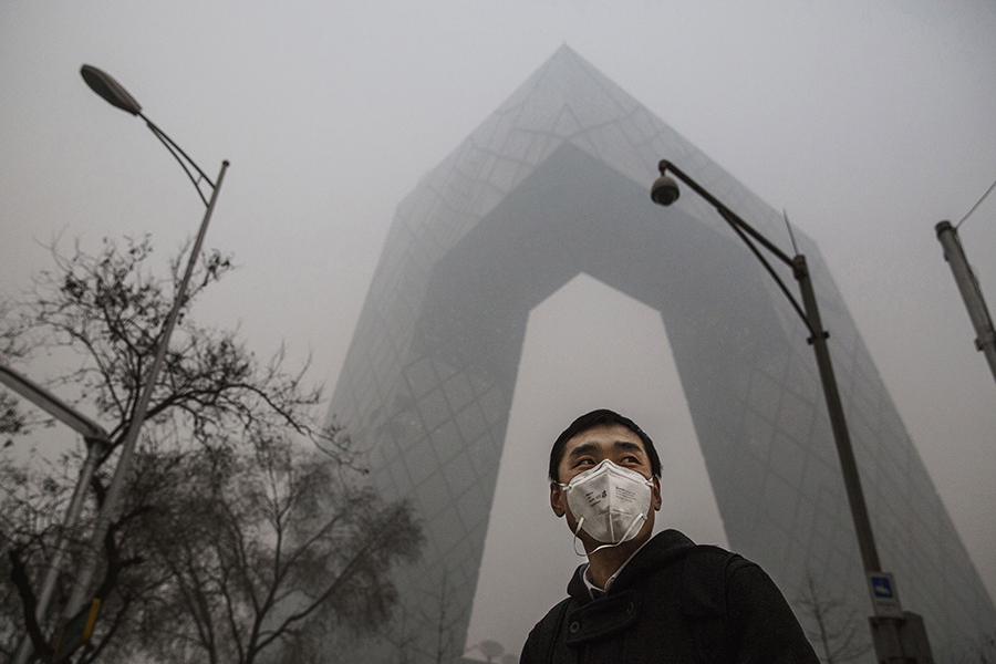A man wears a protective face mask on a smoggy day in Beijing. Credit: Kevin Frayer/Getty Images