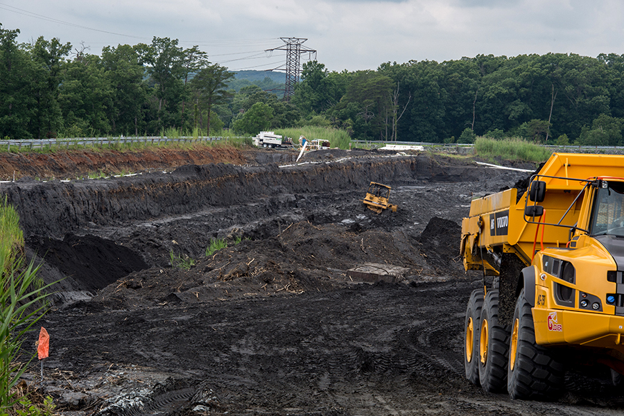 Heavy machinery excavate coal ash from an unlined coal ash pond in Virginia, where a large water release in 2015 had sent the byproducts of coal-burning into Quantico Creek, a tributary of the Potomac River. Credit: Kate Patterson for The Washington Post