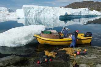 Inuit fishermen prepare a net as free-floating ice floats behind them at the mouth of the Ilulissat Icefjord during unseasonably warm weather on July 30, 2019. Credit: Sean Gallup/Getty Images