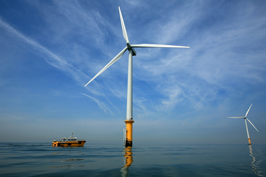 A maintenance boat works next to the turbines in an offshore wind farm near Liverpool, UK. Credit: Christopher Furlong/Getty Images