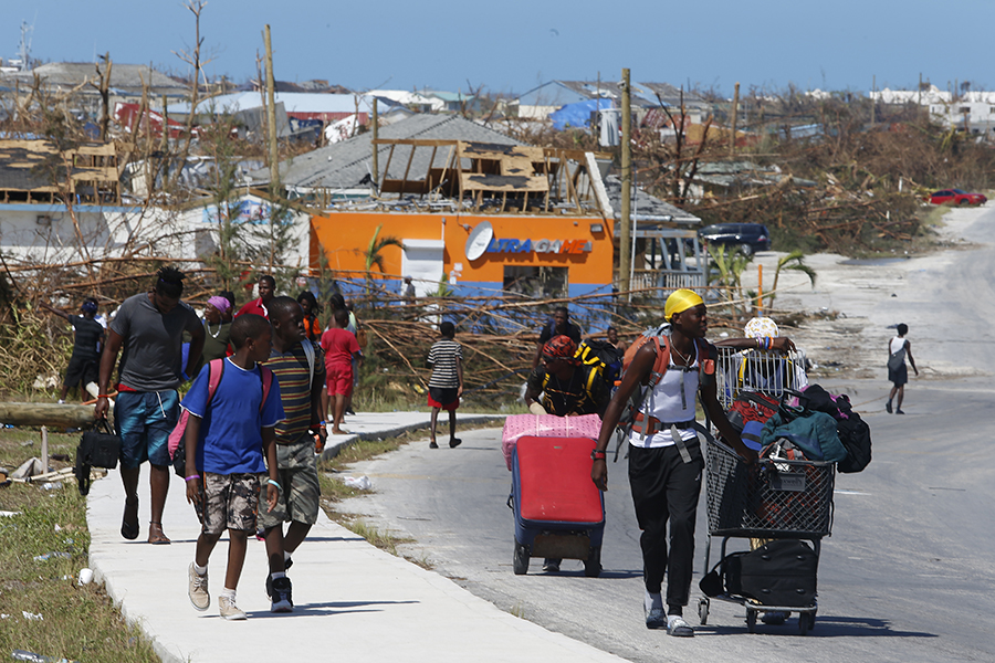 People carried their possessions through what remained of The Mudd area of Great Abaco island on Sept. 5, 2019, five days after Hurricane Dorian struck with Category 5 winds and a powerful storm surge. Credit: Jose Jimenez/Getty Images