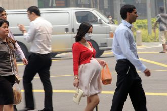 A pregnant woman wears a face mask on a smoggy day in Singapore. Credit: Roslan Rahman/AFP/Getty Images