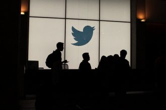 Silhouettes in front of a Twitter logo. Credit: Glenn Chapman/AFP/Getty Images