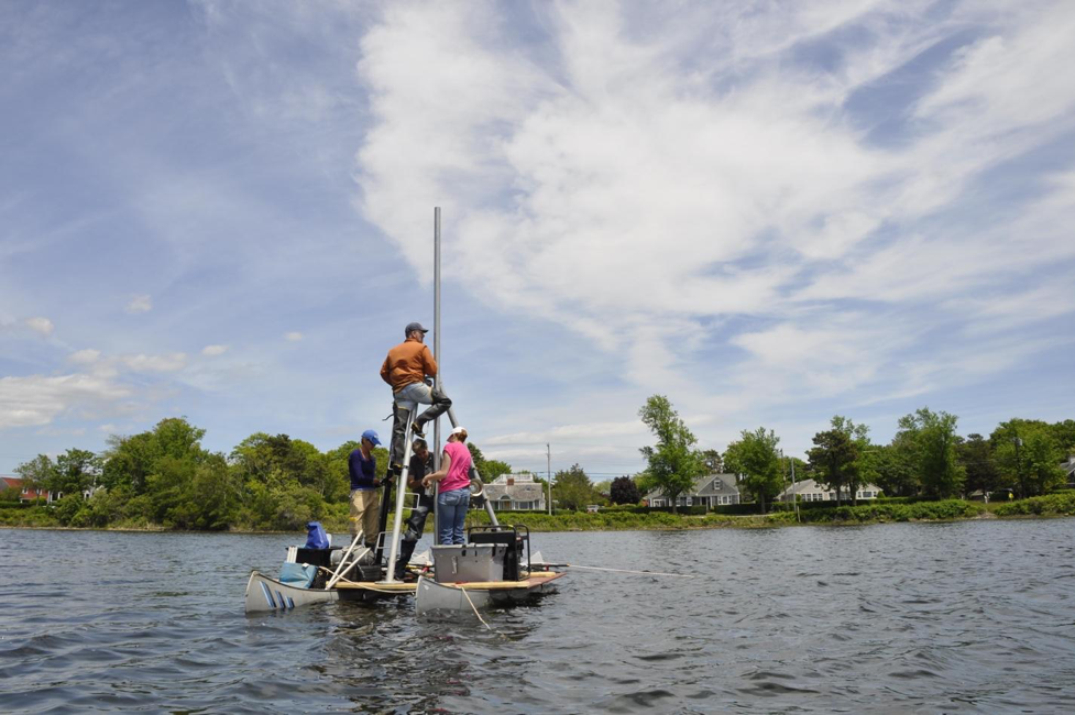 Jeffrey Donnelly, in the orange jacket, and his team collect a sediment core from a coastal pond. Photo courtesy of Jeffrey Donnelly