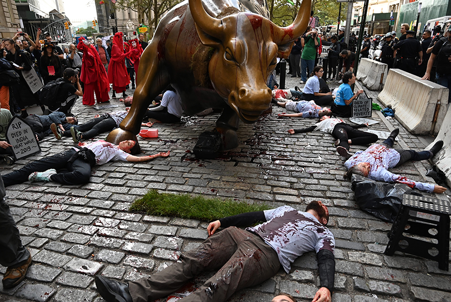Extinction Rebellion protesters covered in fake blood symbolized lives lost to climate-related disasters during a protest on Wall Street in October 2019. Credit: Timothy A. Clary/AFP/Getty Images
