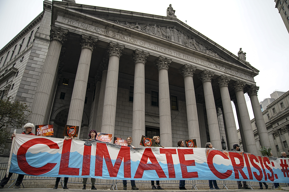 A group of protesters shouted slogans against Exxon outside the New York State Supreme Court building before the start of the trial on Oct. 22, 2019. Credit: Drew Angerer/Getty Images