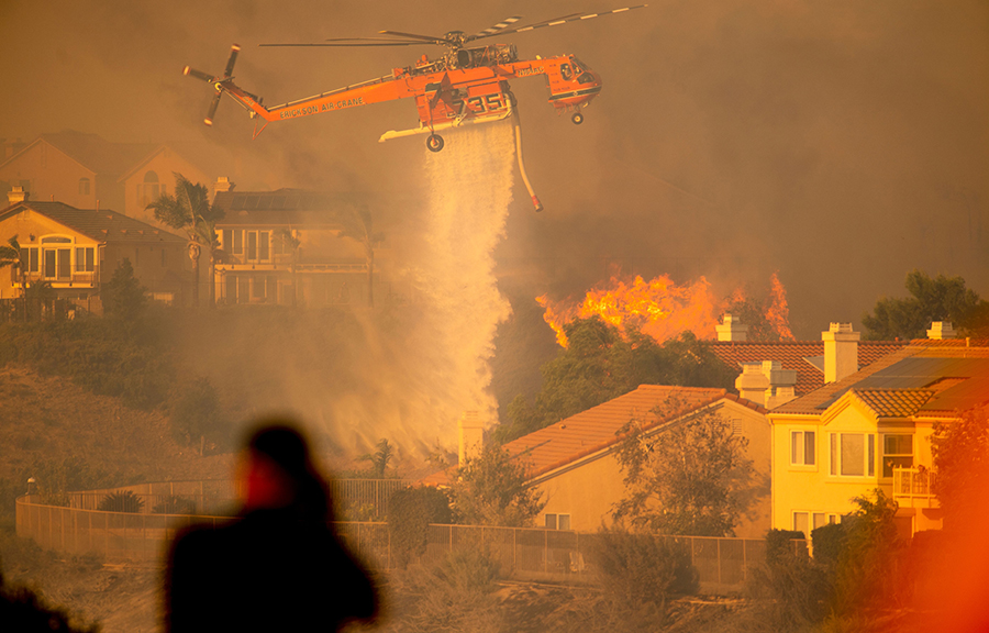 A helicopter dumps water on a fire that broke out near homes in the Los Angeles area in October 2019. Credit: Josh Edelson/AFP/Getty Images
