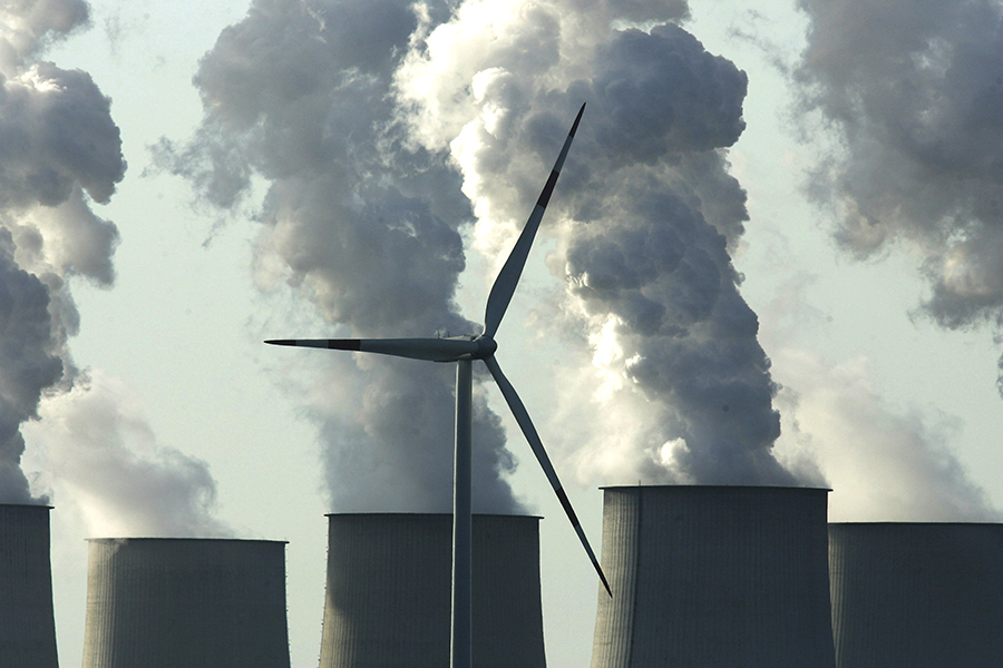 Wind turbine near coal-fired power plant. Credit: Sean Gallup/Getty Images