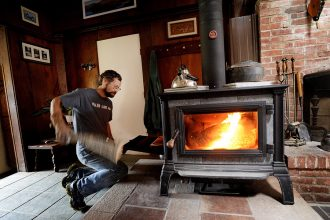 Feeding a wood burning stove. Credit: Shawn Patrick Ouelette/Portland Press Herald via Getty Images