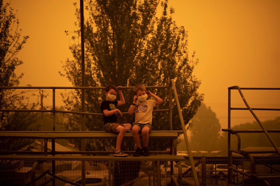 Children wear face masks at the showgrounds in the New South Wales town of Bega where people are camping after being evacuated from nearby sites affected by bushfires on Dec. 31, 2019. Credit: Sean Davey/AFP/Getty Images