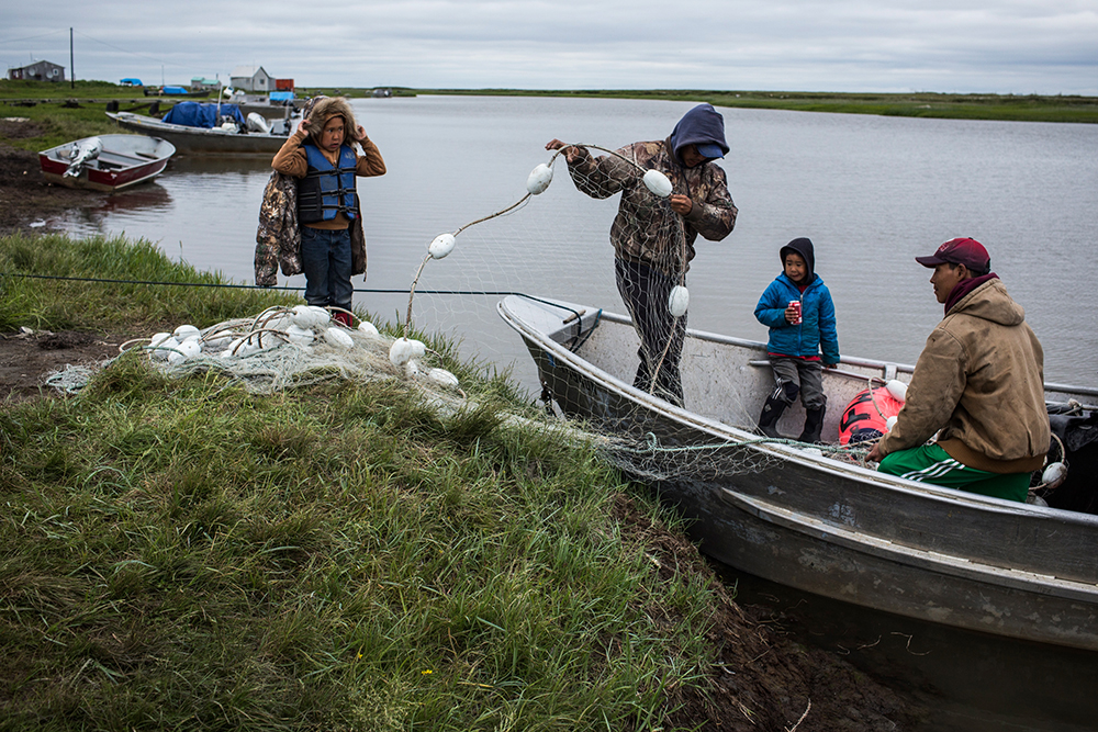 Yupik men prepare a boat to fish for salmon on the Bering Sea. Rising temperatures are affecting their lives in many ways, from the impact on the sea life they depend on for food to sea level rise and erosion that is damaging their coastal communities. Cr