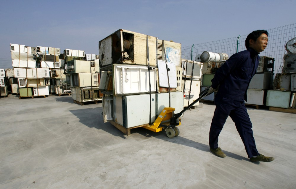 A man pulls discarded air conditioners and refrigerators on a wagon. Credit: STR/AFP via Getty Images