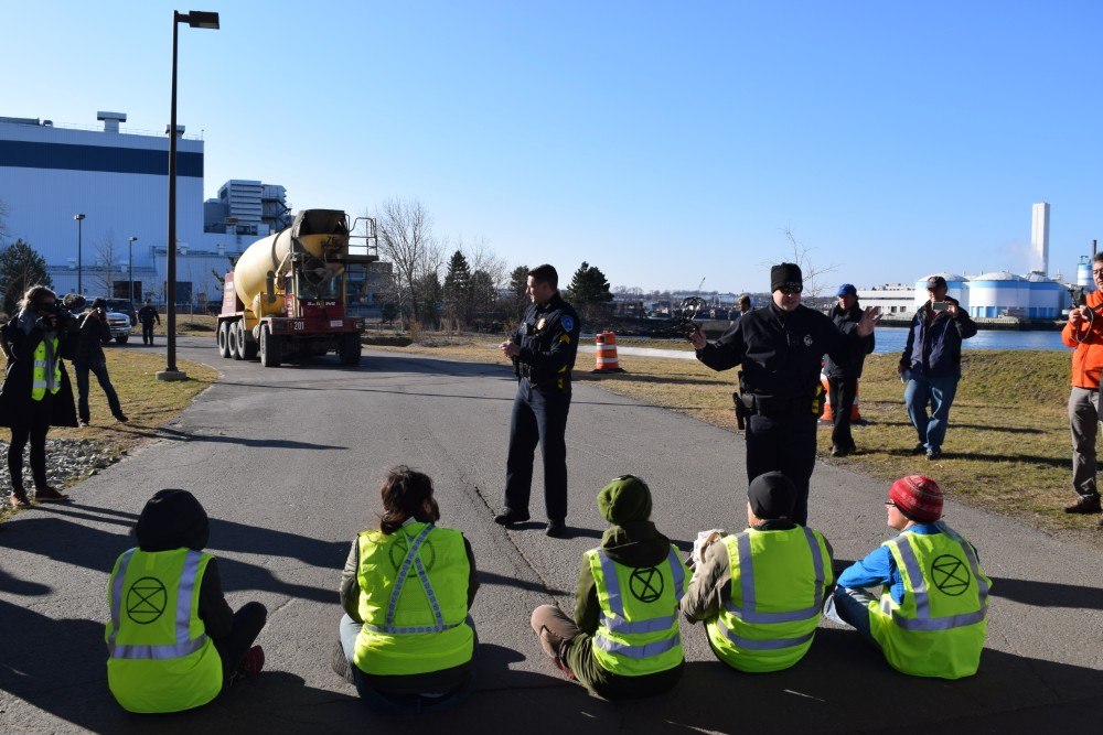 Activists sat in the path of a concrete truck to protest construction of a natural gas compressor outside of Boston near two low-income, environmental justice communities. Credit: Phil McKenna/InsideClimate News