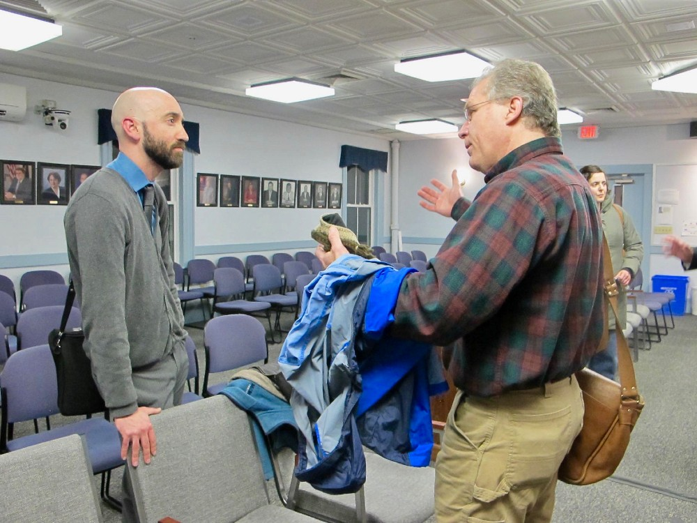 Orion Breen (left), a new community outreach coordinator working with Global Partners, talks to Eben Rose, a member of Protect South Portland. Credit: Sabrina Shankman/InsideClimate News