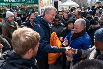 New York Mayor Bill De Blasio hands out reusable bags on Feb. 28, 2020, ahead of a plastic bag ban, The ban was postponed because of the coronavirus pandemic