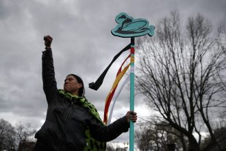 A protester holds a sign during a demonstration against the Dakota Access Pipeline on March 10, 2017 in Washington, D.C. Credit: Justin Sullivan/Getty Images
