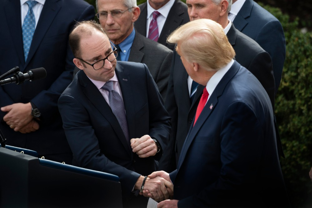 Walgreens President Richard Ashworth shakes hands with President Donald Trump during a press conference on COVID-19 on March 13, 2020. Credit: Jim Watson/AFP via Getty Images