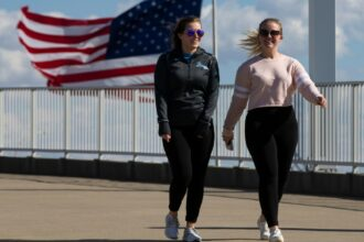 Maggie Olson, left, and Krista Newton enjoy a walk on the Big Four Bridge in Louisville, Kentucky, while they make the most of the sunny skies and temperatures above 60 degrees Tuesday, March 3, 2020. Credit: Alton Strupp/Courier Journal