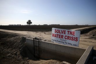 A sign referencing the drought is posted next to a fallow field on April 24, 2015 in Lemoore, California. Credit: Justin Sullivan/Getty Images