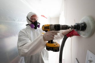 A Veterans Green Jobs employee drills holes to blow cellulose insulation in the interior walls of this Colorado home undergoing weatherization. Credit: Dennis Schroeder/NREL