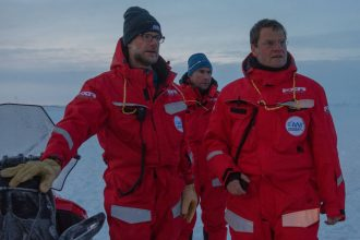 Expedition co-cruise leader Matt Shupe, left, and Marcel Nikolaus join MOSAiC expedition leader Markus Rex, right, in front of Polarstern icebreaker. Credit: Esther Horvath/Alfred-Wegener-Institut