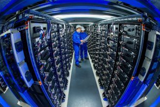 Trainees check the connections a row of power storage units in a commercial battery facility in Schwerin,Germany. Credit: Jens Büttner/picture alliance via Getty Images