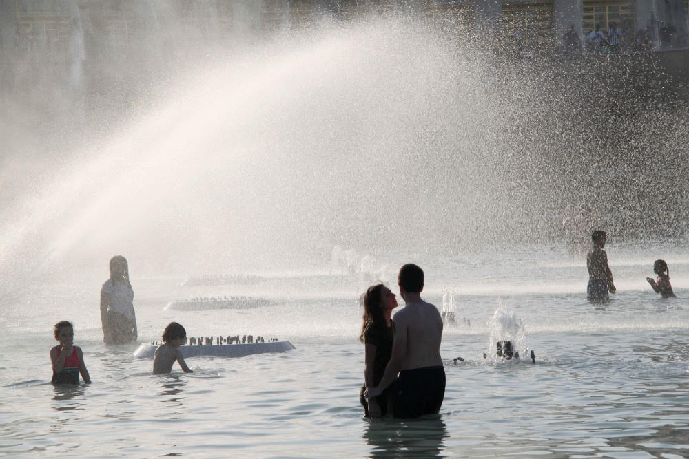 People cool themselves at a fountain opposite the Eiffel Tower during a heat wave on June 27, 2019 in Paris, France. Credit: Li Yang/China News Service/Visual China Group via Getty Images