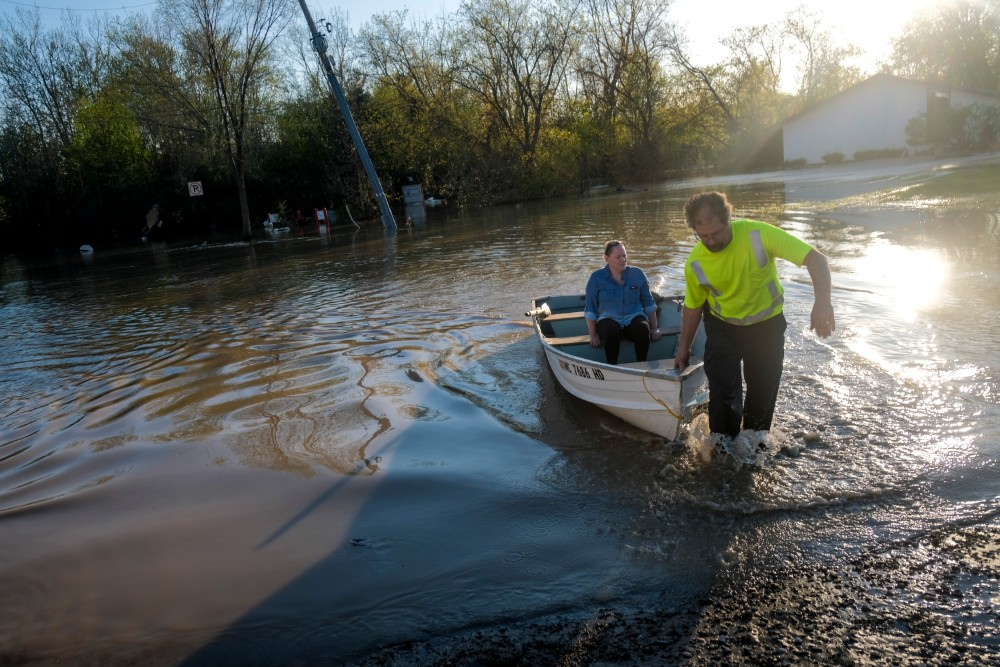Neil Hawk and his wife Dawn take a rowboat to inspect the damage to their neighborhood following extreme flooding throughout central Michigan on May 20, 2020 in Sanford, Michigan. Credit: Matthew Hatcher/Getty Images