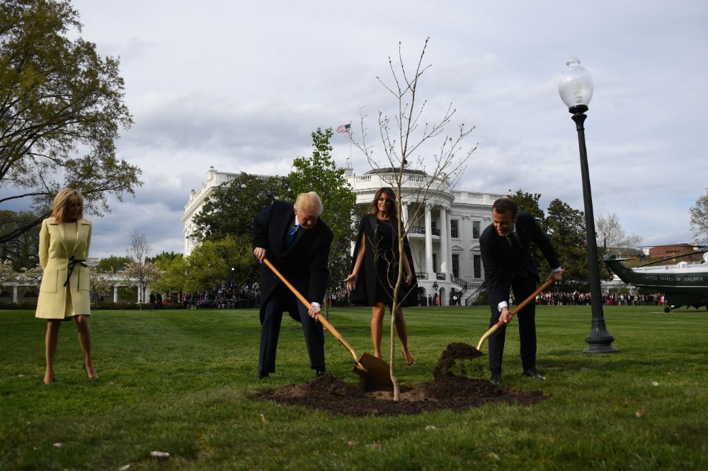 President Donald Trump and First Lady Melania Trump participate in a tree planting ceremony with French President Emmanuel Macron and his wife Brigitte Macron on the South Lawn of the White House on April 23, 2018. Credit: Jim Watson/AFP via Getty Images