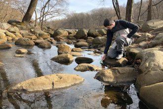 Liam McGrath, a Manhattan College student and citizen scientist with Van Cortlandt Park Alliance, dips a water quality probe into Tibbetts Brook. Credit: Maddie Kornfeld