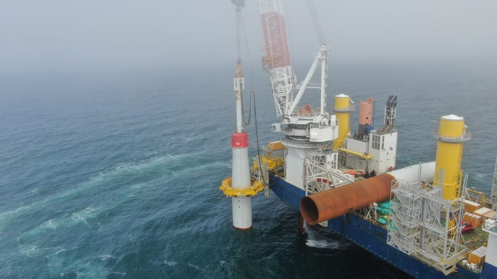 Workers install the foundation of a wind turbine that is part of the Coastal Virginia Offshore Wind project, developed by Ørsted, the Denmark-based power company. Credit: Dominion Energy