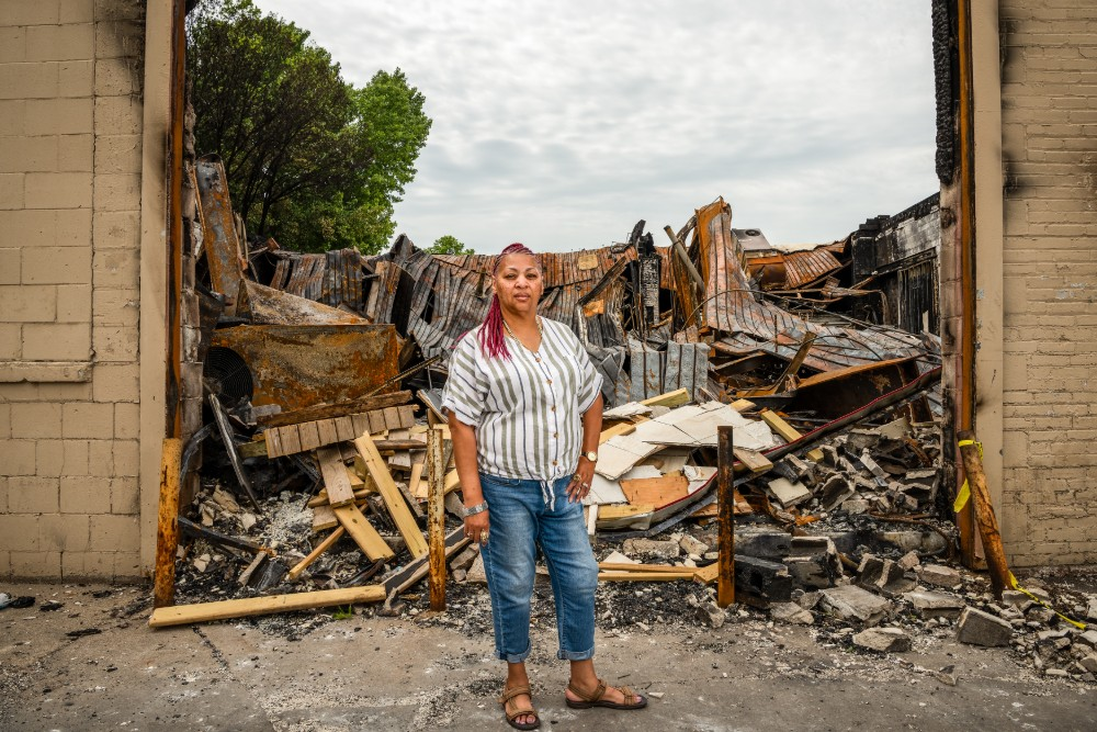 """Maleta """"Queen"""" Kimmons stands at the North Minneapolis O'Reilly Auto Parts store on Broadway Ave. The store was destroyed during a recent demonstration for George Floyd. Credit: Katie G. Nelson"""